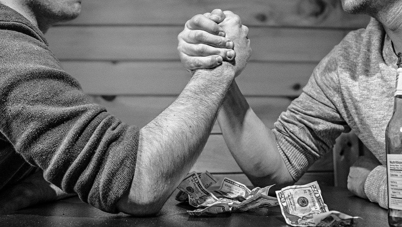 Two men arm wrestling over crumpled up cash in black and white