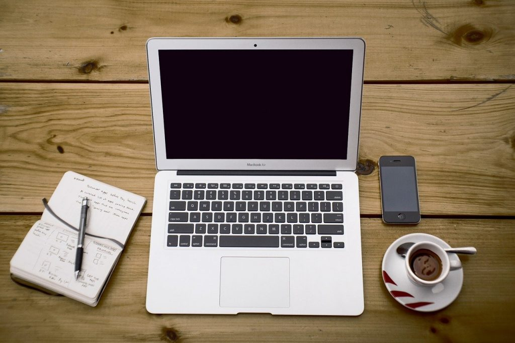 A laptop, phone, notebook, and coffee sitting on a desk