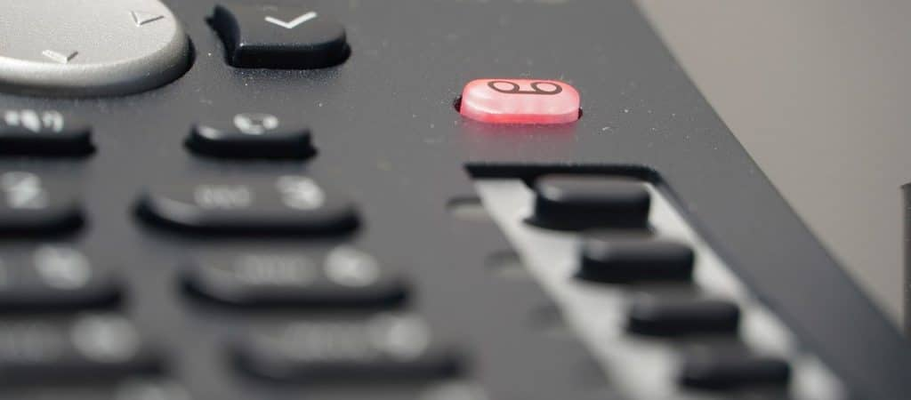 Close up of a desk phone voicemail button
