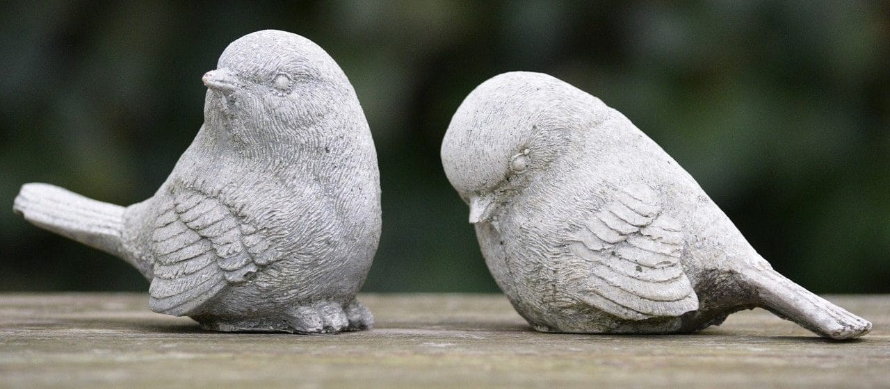 Two small bird statues looking away from each other